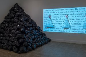 Black trash bags piled up into a pyramid in the corner of a room to the left, and a projection of text over three white trash bags hanging on the wall to the right.