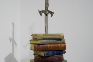 A stack of books pieced by a sword.