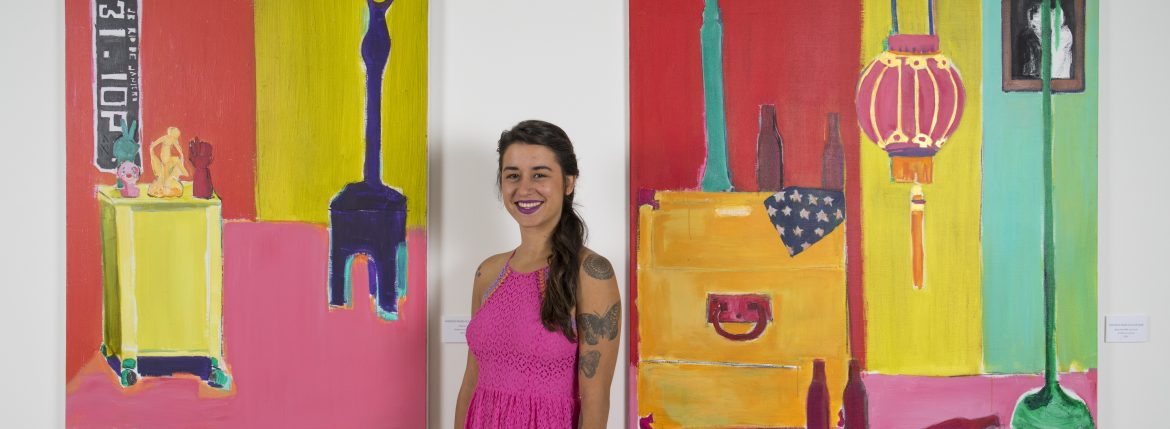 Natasha Radovicz Schaidt pictured between two paintings entitled Clownin' and Beers with Billie.