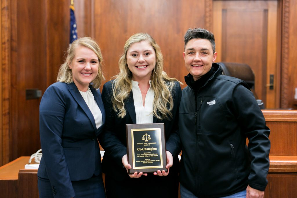 Sara Papantonio (left) and Raelyn Watson (center) won the regional National Trial Competition in Alabama and will head to the national finals in Texas in April. The winners are pictured here with their coach, Professor Julia Metts.
