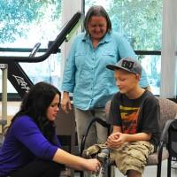 IHSC alum Rachel Friddle and Prof. Michele Skelton help child for prosthetic leg.