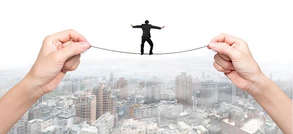 graphic art: illustration of man balancing on tightrope