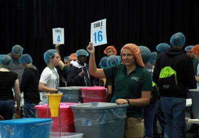Big room full of volunteers with food supplies