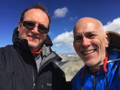 A smiling Nestor de Armas and David Collis on a mountaintop