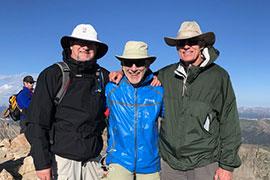 Three men standing arm in arm on Colorado mountain top