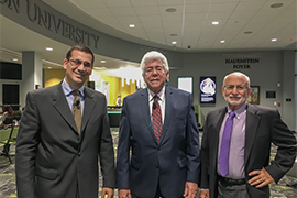 Three men stand side by side in the Rinker Welcome Center lobby.