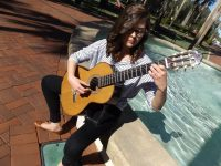Lauren Baucum plays a guitar seated beside Holler Fountain on Stetson University's DeLand campus.