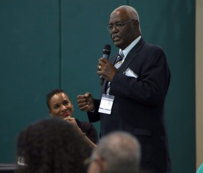 Jim Johnson stands in the front of the crowd with a microphone as Gwen Azama-Edwards listens on the panel