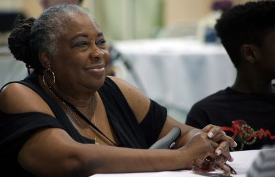 Dottie Johnson sits listening at a banquet table in the Rinker Field House