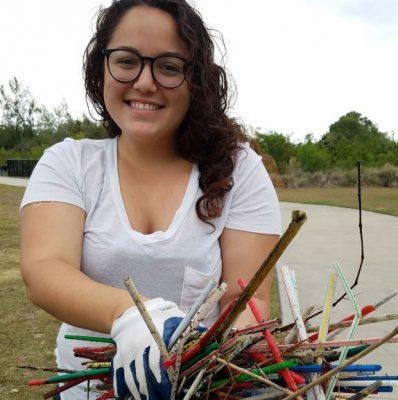 Jennifer Winn holds a mess of plastic straws and other debris