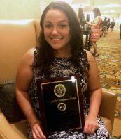 Jennifer Winn sits in a chair holding her award.