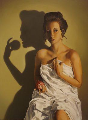 A woman sits holding a half-eaten apple.