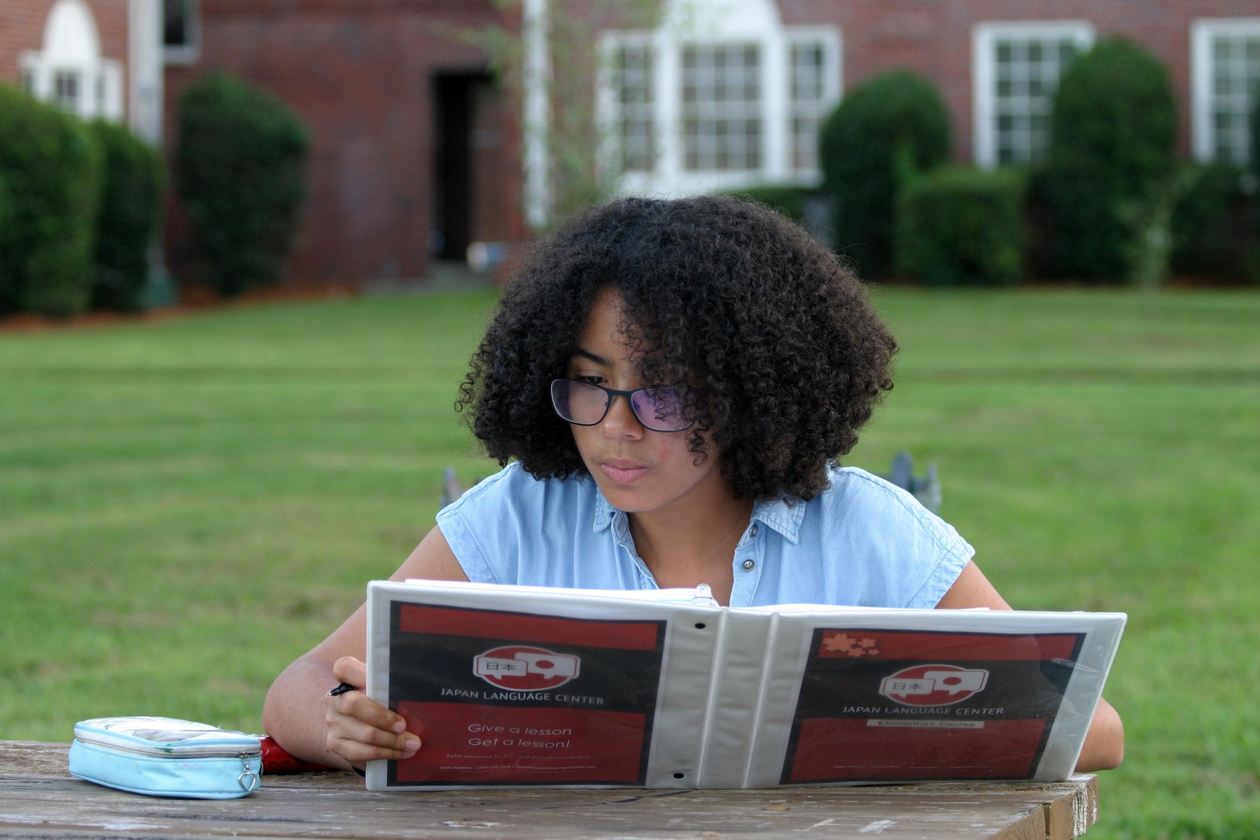 Sinai Ramos sits at a table outside Gordis Hall, reading a Japanese textbook.
