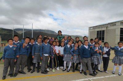 Rajni Shankar Brown stands amid a group of young schoolchildren.
