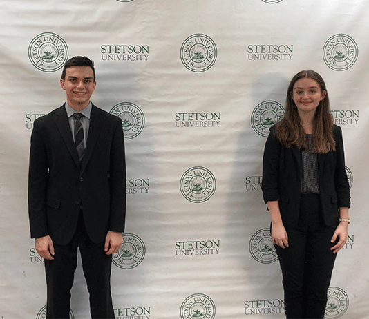 The two students stand in front of a background with Stetson University and its seal.