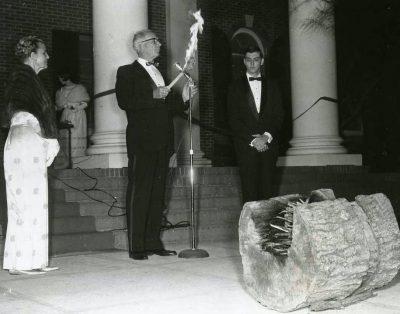 Dean Etter Turner and President J. Ollie Edmunds, in formal attire, prepare to light the Yule Log.