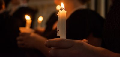 closeup of choir members hold candles