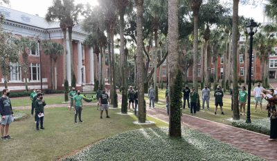 Students stand in Palm Court, physically distanced and wearing masks, to perform.
