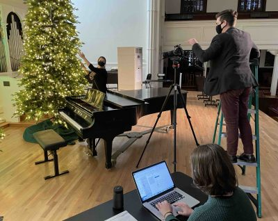 A stage crew set up a camera in front of a piano and a Christmas tree in Lee Chapel