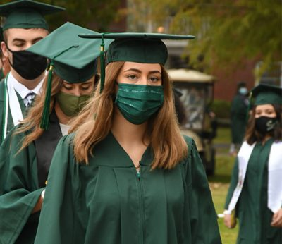Graduates walk to Commencement in caps, gowns and face coverings.