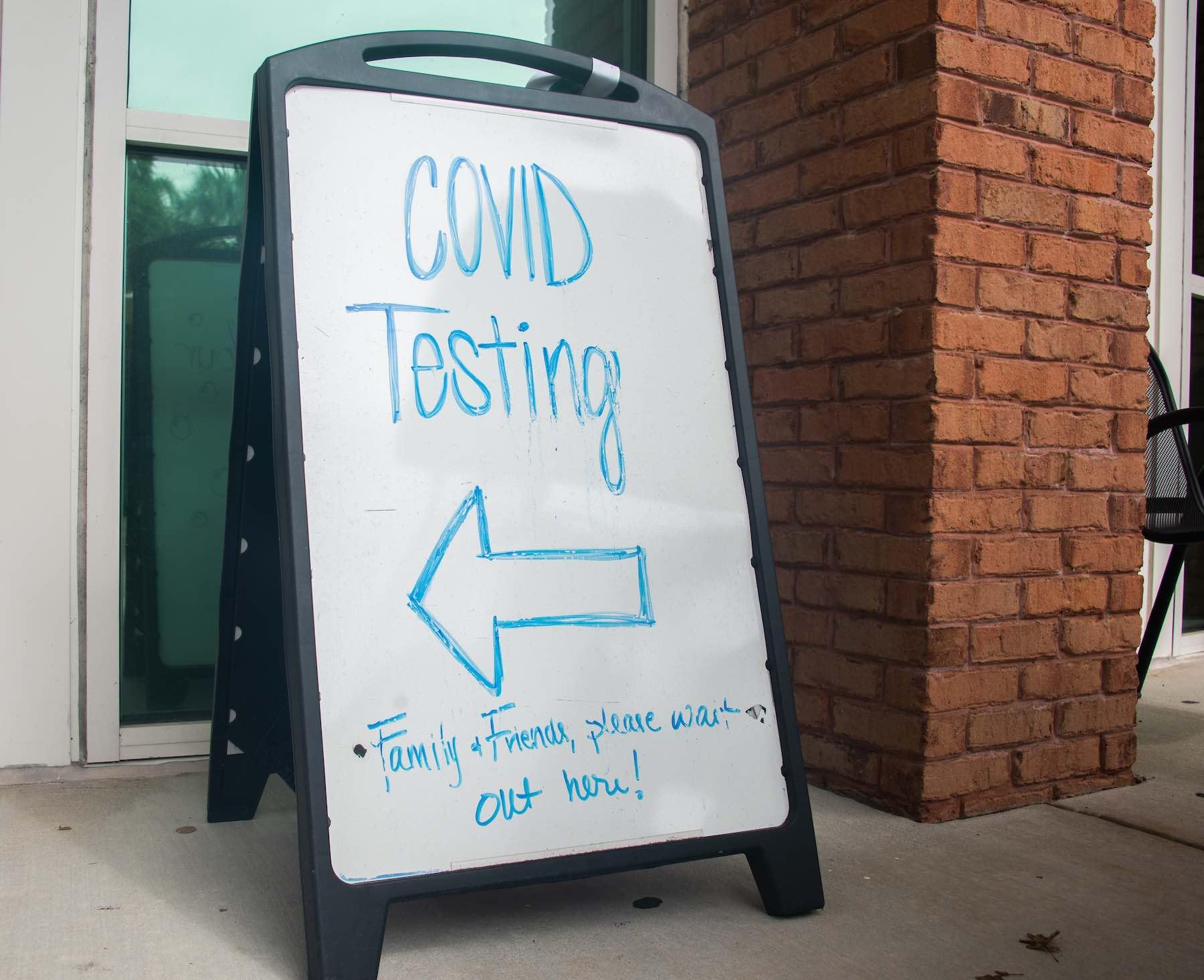 A sandwich board sign says COVID-19 testing