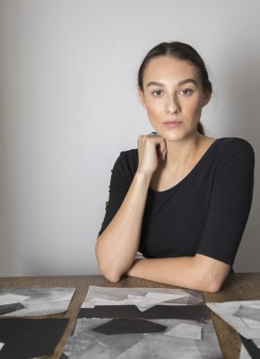 portrait at table with pieces of artwork.