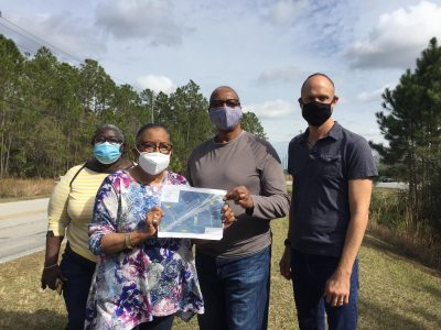 Four people post as two hold a map alongside State Road 92, west of Daytona