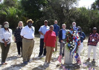 A group of people stand around a grave marker adorned with flags and red and white flowers.