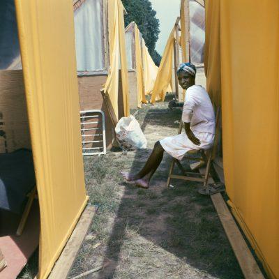 A woman sits between makeshift tents, 1968