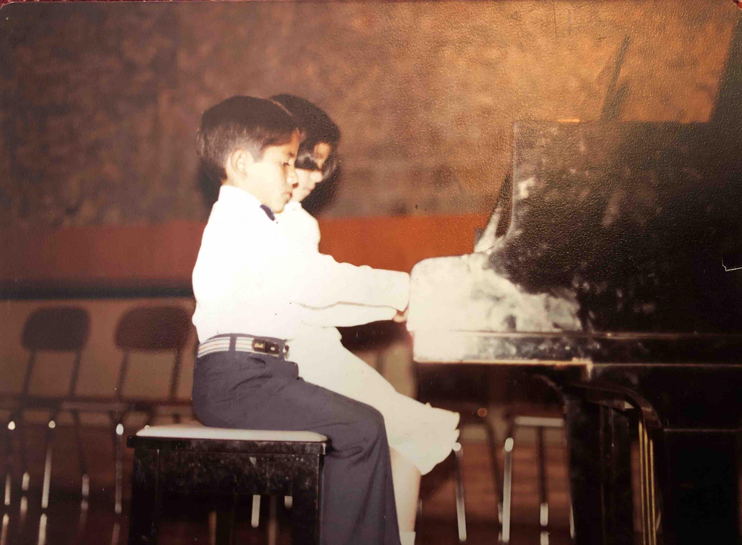 Washington Garcia, as a boy, pratices piano beside his sister.