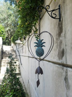 A bell hangs from the garden wall
