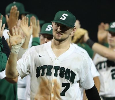 Andrew MacNeil gives a high five to opposing player after baseball game