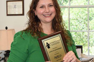 Lynn Schoenberg holds her award.