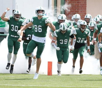 The Hatters football team runs onto the field.