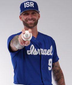 Nick Rickles wears the Israel national team baseball uniform and holds a baseball.