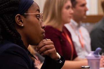 Participants listen at a meeting