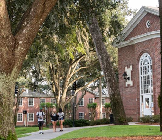 3 students walk across campus.